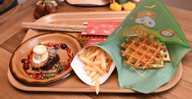 「キャンプ・ウッドチャック・キッチン」で提供される新メニュー。左から「スモア風チョコレートブラウニー」(400円)、「フレンチフライポテト」(220円)、「ワッフルサンド(スパイシーシュリンプ&アボカド)」(700円)。ワッフルサンドはほかに「フライドチキン、メイプルソース付き」と「ベーコン、ベジタブルBBQソース」を用意