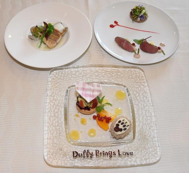 ホテルミラコスタの地中海レストラン「オチェアーノ」で提供されているスペシャルメニュー「スウィート・ダッフィー」ランチコース(〜2月14日)。「イトヨリ鯛のポワレ ワカメと大麦のカルドソフェンネルのフォームと共に」(後左)、「鴨胸肉のロースト アンディーヴとナッツのサラダ仕立て  レッドカラント風味のレムラードソース」(同右)、と「ピスタチオのクリーム チェリーとクランベリーのコンフィチュール ミルクティーアイスを添えて」(手前)