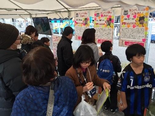 遠藤保仁選手らG大阪3選手の「元気めし」についての寄せ書きを熱心に読むサポーターら