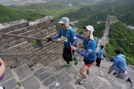 万里の長城は、階段の段差、面の奥行きも同じものがない。 伴走者は、段差があると「up !」、大きな段差には「big up !」 と声をかけ、視覚障がいランナーに伝える。(写真・Small Bell Sound)