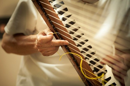 箜篌の復元制作の最終仕上げは、絹糸のチューニングだ。そもそも轉軫箜篌の「轉軫」(てんじん)とは糸巻のこと。器用に絹糸を張って調弦していく。