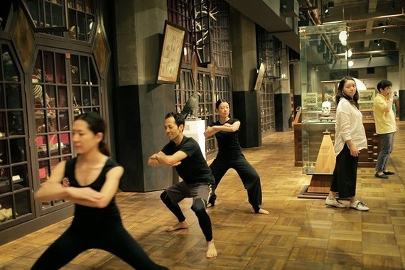 右端の黄色のシャツの男性が演出家の金世一氏。標本の間を練り歩く役者たちの動きを見守る。脚本を練りながら、10月から制作に入る。