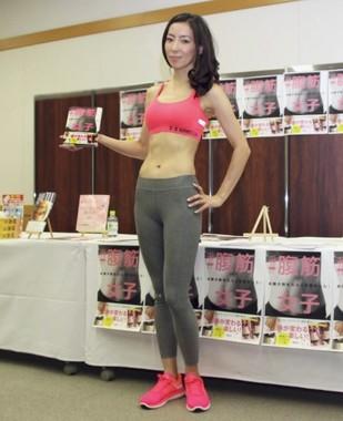 新刊『#腹筋女子 お腹が割れたら人生かわった!』を手にする山崎麻央氏
