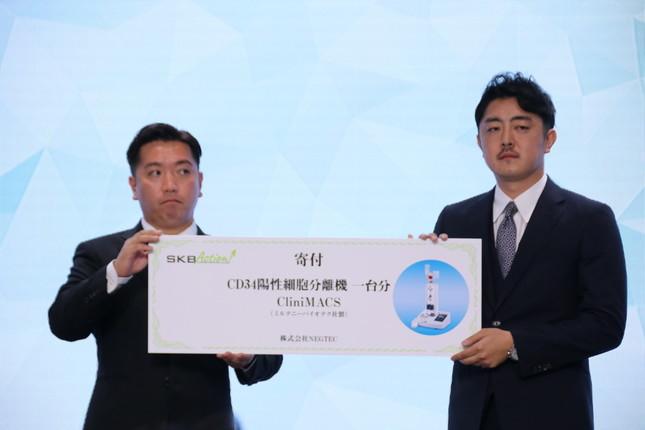 チャットドクター・草野正臣社長(写真右)に、「クリニーマックス」1台分の寄付を贈呈した(2018年8月撮影)