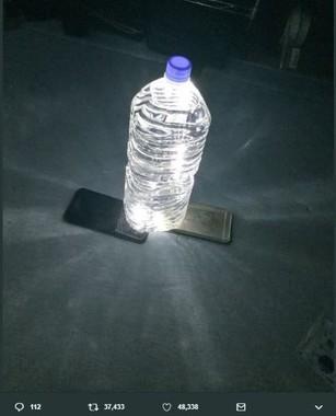 水の入ったペットボトルの下から、携帯電話のライトを当てる(あやとさんのツイッターより)