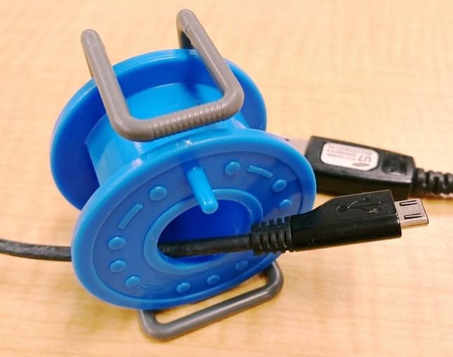 USBケーブルの先端を穴に通して、リールを時計回りにまわして巻く