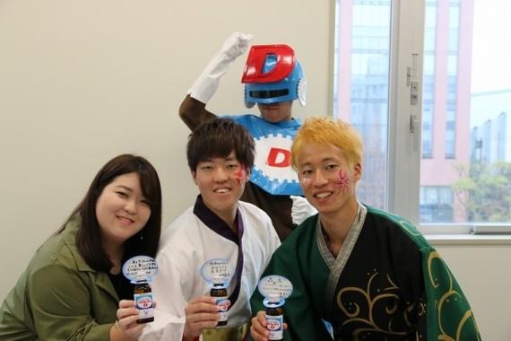 リポビタンDを贈る赤羽美香さん(左)と、関東学院大学「誇咲」の赤羽亮太さんと山﨑湧太さん。そして背後のヒーローは何者?
