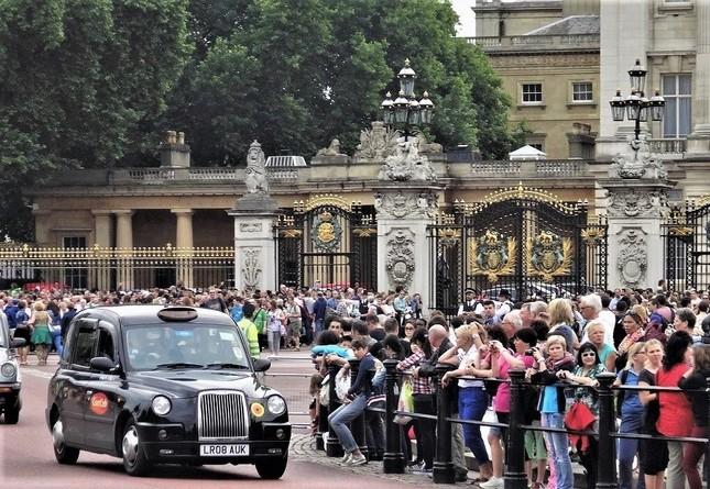季節を問わず大勢の観光客でにぎわうロンドン中心部=バッキンガム宮殿前で、冨永写す
