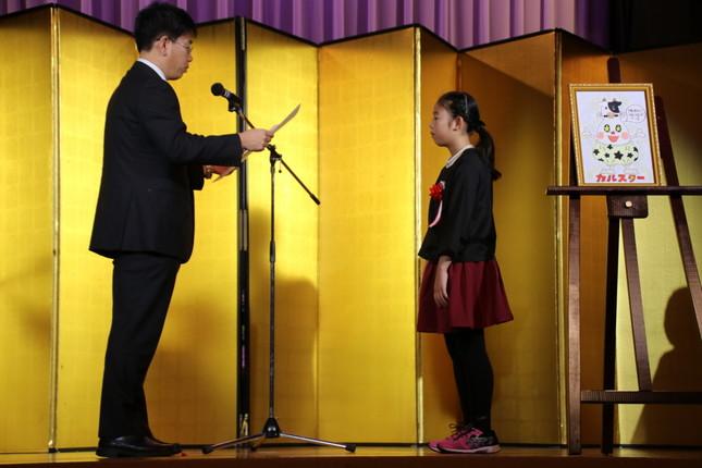 (左から)農林水産省の葛谷好弘氏、農林水産大臣賞を受賞する時田波乃帆さん