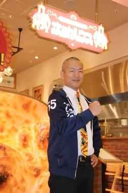 「ゴーゴーカレー」に続くブランド「ホットハウス」の店舗前で、「55」と記されたパーカーを切る宮森CEO
