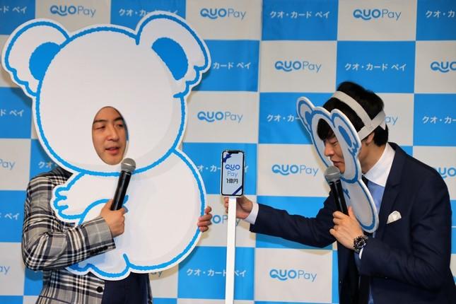 「QUOPay1億円」と画面表示されたスマートフォンが登場