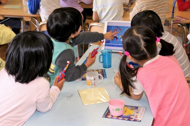 机に置かれたiPadに興味津々の園児たち