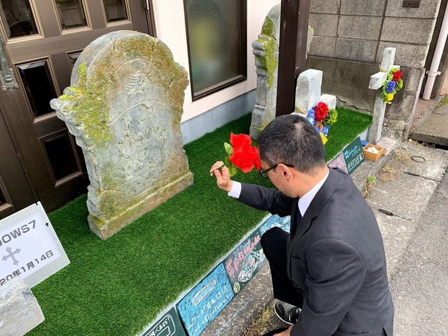 墓前で祈りをささげるいっとくの永野間社長