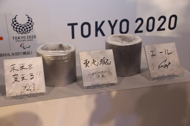 圧縮したアルミ材(奥)と3人のサイン(手前)