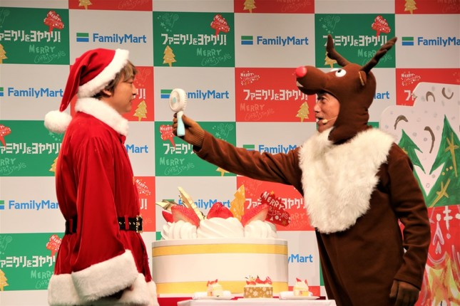トナカイ姿のファミリーマート澤田社長(右)に小型扇風機を当てられる香取さん