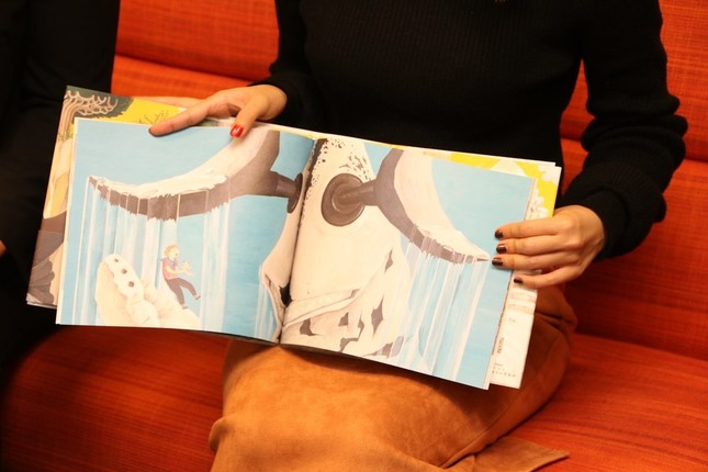空想科学絵本「かいじゅうのすみか」を開き、物語を説明する円谷プロダクション担当者
