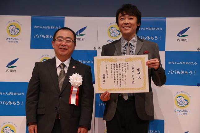 大臣官房総括審議官の渡邉清さんと任命状を持つ小林さん(左から)