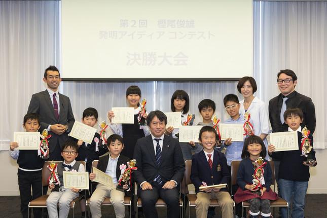 コンテストの審査員委員長の樫尾隆司さん(中央)と決勝大会に参加した小学生たち