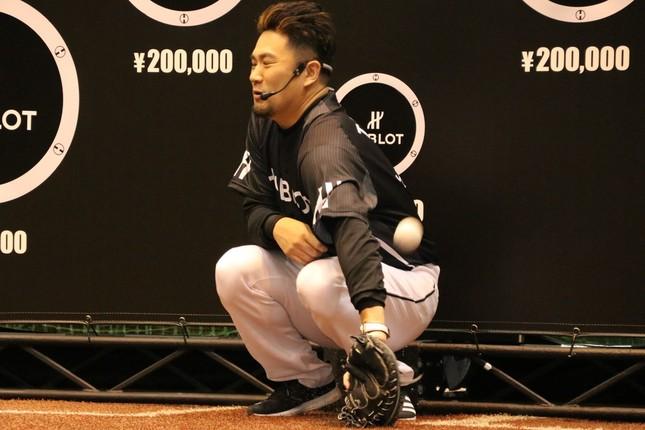キャッチャーとして子供の投げたワンバウンドボールを取る田中選手