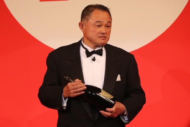 表彰を受け、副賞のワインを手にスピーチをする山下泰裕さん