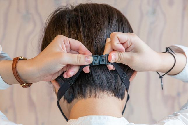 アジャスター付きゴムを調節して後頭部か首の後ろに回し、薄型のバックルで止める