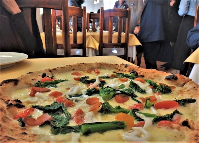 白魚と菜の花、カラスミのピザ。チーズの上で山海の旬が融け合う=世田谷区で、冨永写す