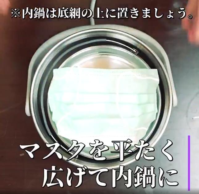 「電鍋」の蓋を開け、マスクを平たく広げて内鍋に入れる