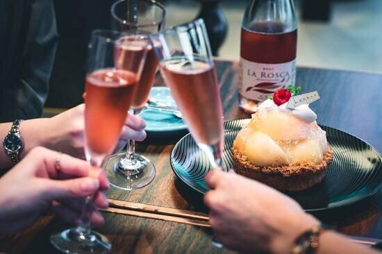 ケーキ、花、スパークリングワインでお祝い