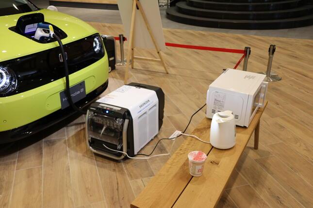 外部給電器を使い、実際に電子レンジと電気ケトルに給電している様子