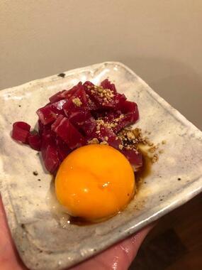 卵黄をトッピングした「ごま油で食べる牛生ハム」(ココニャさんの提供)