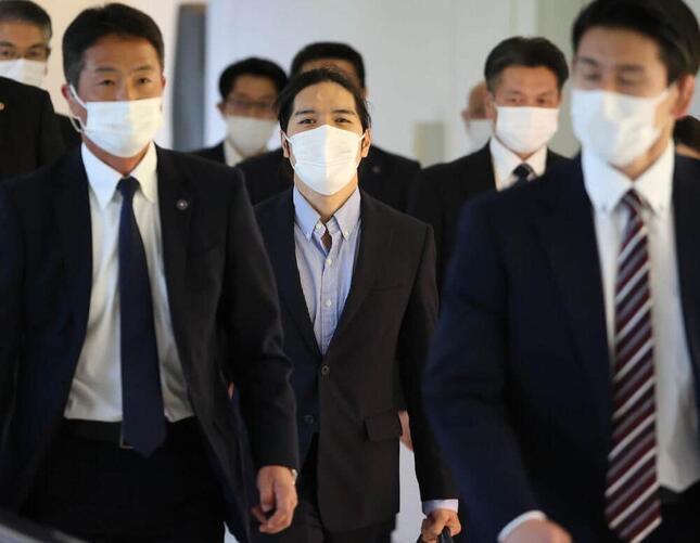 帰国し関係者に囲まれながら歩く小室圭さん(写真:つのだよしお/アフロ)