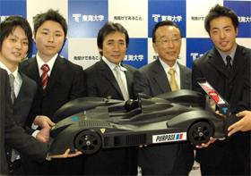 マシンの模型を手にル・マン参戦を発表する東海大学の林義正教授(右から2人目)とドライバーの鈴木利男氏(同3人目)と学生ら