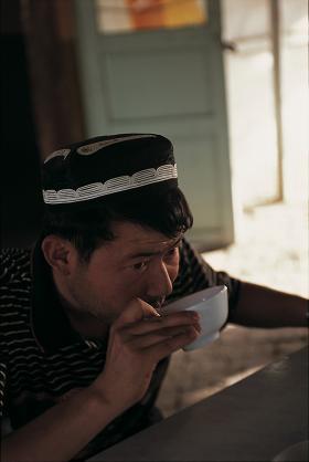 「朝食に茶(レンガ茶)をのむウイグル人。中国・トルファン」(04年4月撮影)