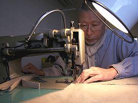ミシンに向かう須田栄一さん。木綿の9号帆布、縫い糸はナイロン製。デザインによって布も糸もオリジナルの色に染める。