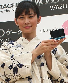 「Woooケータイ」を手にポーズをとる伊東美咲さん