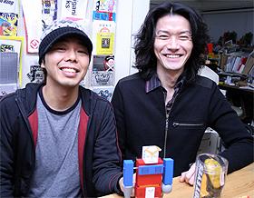 脱力系のユニークな商品を生み出している、ザリガニワークスの武笠太郎さん(左)と坂本嘉種さん(右)。手前が「コレジャナイロボ」