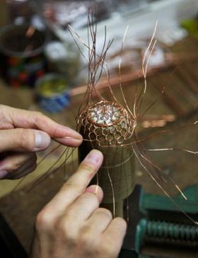 柔らかな銅線をよじり、ひと目ずつ丁寧に編み上げる茶こし。底には菊の花模様、側面は亀甲に編み上げる。