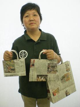新聞バッグを手にする伊藤さん