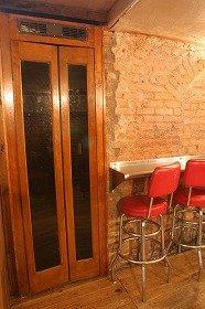 アンティークの電話ボックスにかかった受話器で話すと中からドアを開けてくれる(「PDT」)