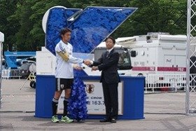 楢崎選手(左)と握手を交わす加藤利夫・ファミリーマート取締役常務執行役員(22日、東京・代々木で)