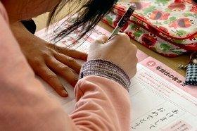 教材を見ながら年賀状の書き方を学ぶ