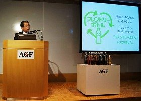 2011年11月21日、都内で記者会見を行う村林誠社長。表示されているのはフレンドリーボトルのロゴマーク