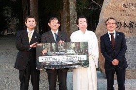 寄付金贈呈式後のフォトセッションでカメラに収まる、仁坂・和歌山県知事(左から2人目)とKDDI・甘田関西支社長(19日、和歌山県内で)