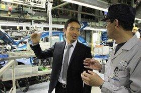 マツダの工場で社員の説明を受ける長友選手(左)