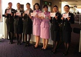 客室乗務員はピンクのスカーフを着用し、搭乗ゲートのスタッフ(中央2人)はラウンジ用のピンクの制服で乗客を見送った