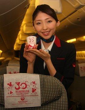 機内では、特別デザインのヘッドレストカバーと紙コップが出迎える。客室乗務員(CA)が着ているのは6月から導入が始まる新制服