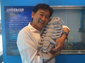 「ダイオウグソクムシ」のぬいぐるみを抱く石垣幸二さん