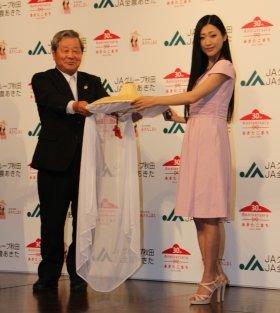 JA全農あきた運営委員会会長・木村一男氏から「市女笠」を渡される壇蜜さん