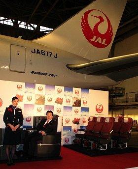 ボーイング767型機向けビジネスクラスんのシートに腰掛ける植木義晴社長(左)。右側はエコノミークラス向けシートだ