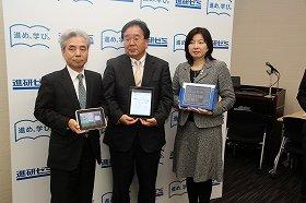 タブレットを持った福島保社長、明田英治社長、成島由美本部長